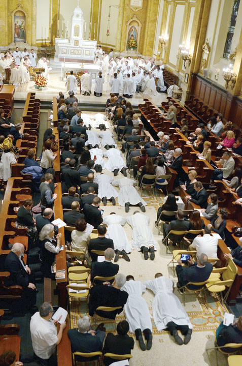 Deacon candidates lay prostrate on the chapel floor during the ordination rite.