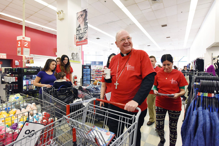 Cardinal Dolan looks for items on his list.