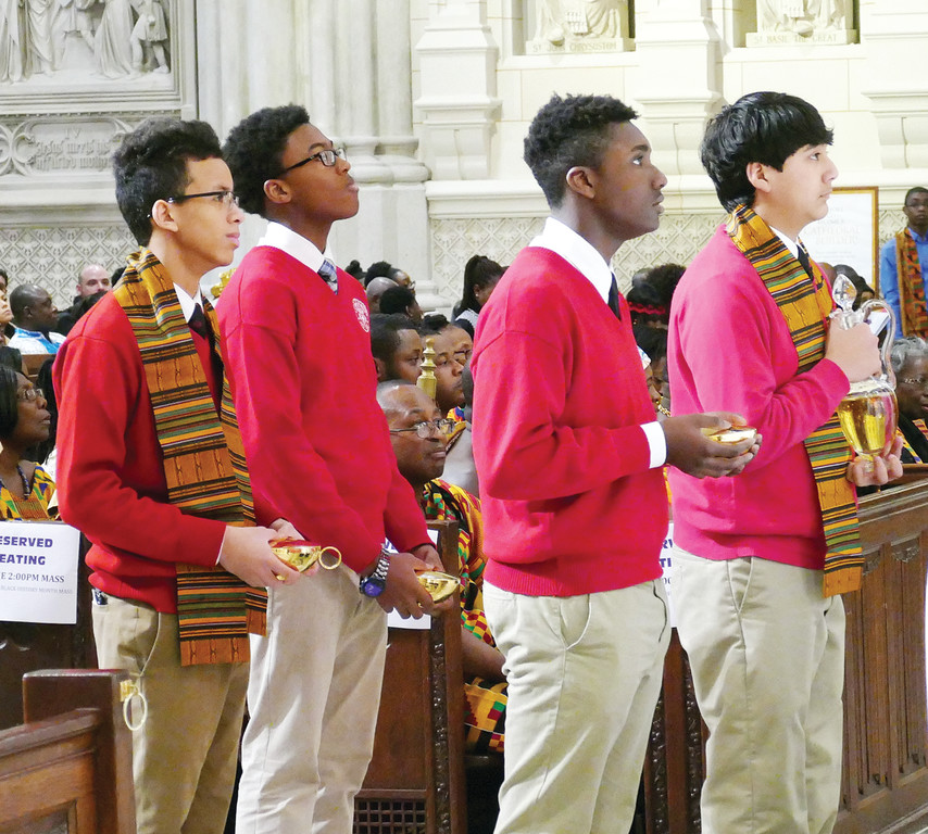 La Salle Academy students, from left, Jayden McCoy, David Goudet Turner, Rohan Tucker and Joseph Palaguachi bring forward the offertory gifts.