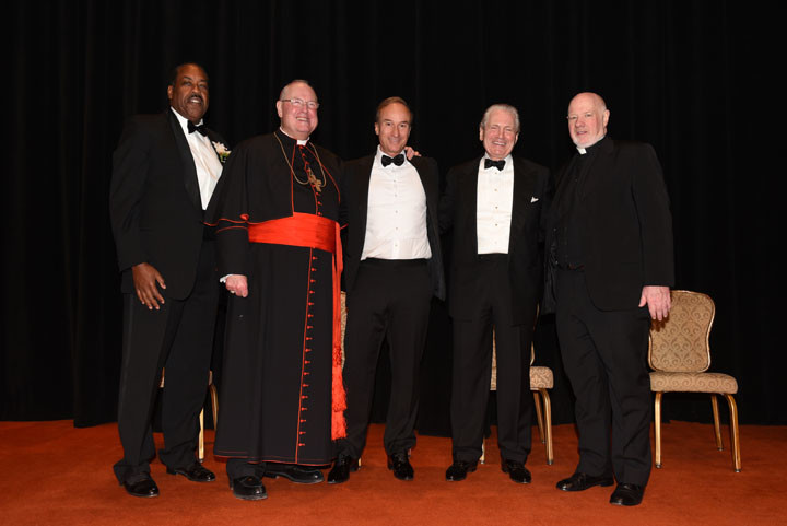 Cardinal Dolan and Msgr. Kevin Sullivan, executive director of Catholic Charities, are joined at the Catholic Charities Gala at the Waldorf Astoria March 9 by Stanley E. Grayson, far left, senior vice chairman of the Catholic Charities board of trustees, and Deus Caritas Est Award recipients Stephen C. Freidheim and J. Tomilson Hill.