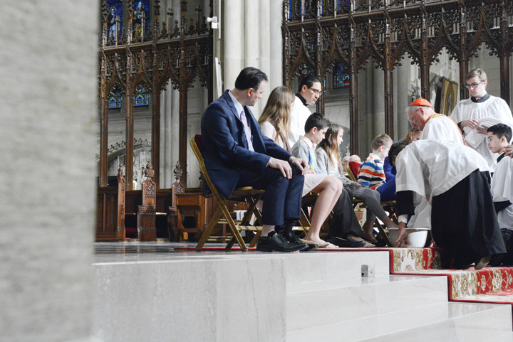 Cardinal Dolan leads a Eucharistic procession in St. Patrick's Cathedral at Mass of the Lord's Supper March 24, center left, and washes the feet of 12 men, women and children as Jesus washed the feet of his disciples as a sign of service.