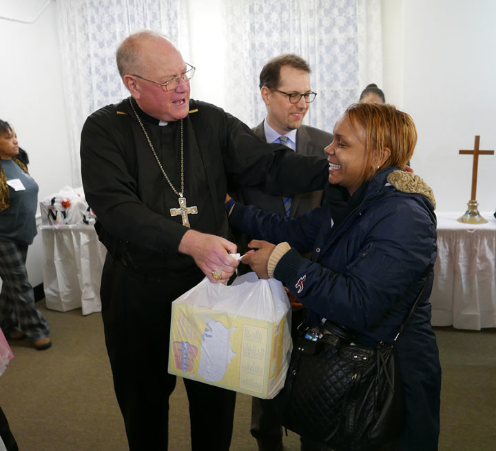 Cardinal Dolan gives out food on Holy Thursday at the Washington Heights Ecumenical Food Pantry. The pantry is a Catholic Charities center.