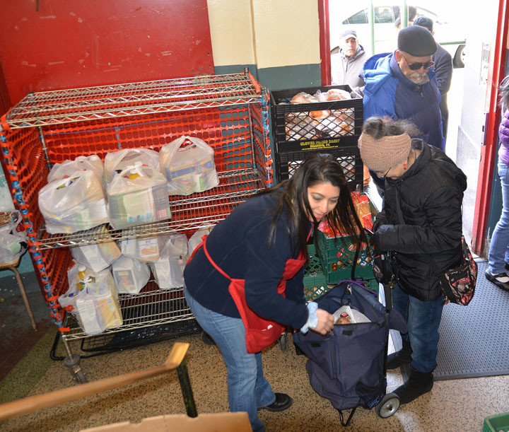A staff member of the Washington Heights Ecumenical Food Pantry gives goods to those in need on Holy Thursday, March 24.