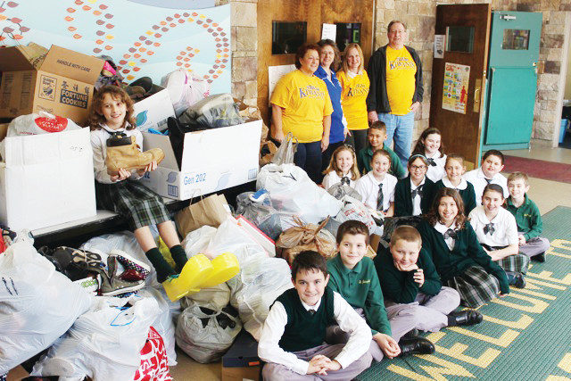 Rose Dermody, far left, a fourth-grader at St. Joseph's School in Kingston, wears big shoes in yellow to highlight the 1,008 pairs of shoes the class collected for the needy.
