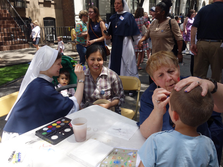 Sister Jordan Rose, S.V., with a volunteer, paints faces at the Sisters of Life block party in celebration of the 25th anniversary of the congregation's founding. The block party was held on 51st Street between 9th and 10th Avenues after a morning Mass at St. Patrick's Cathedral June 1.
