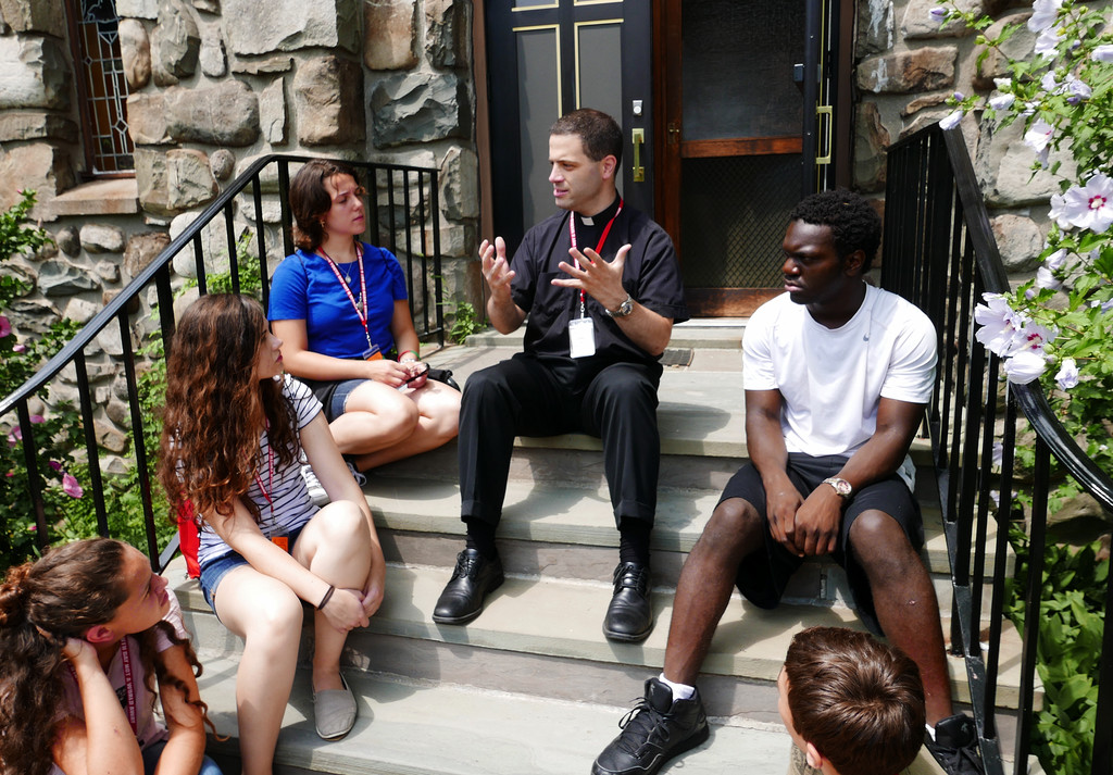 Father Christopher Argano, new director of vocations for the archdiocese, speaks with teens and young adults outside the chapel at Marycrest on July 30.