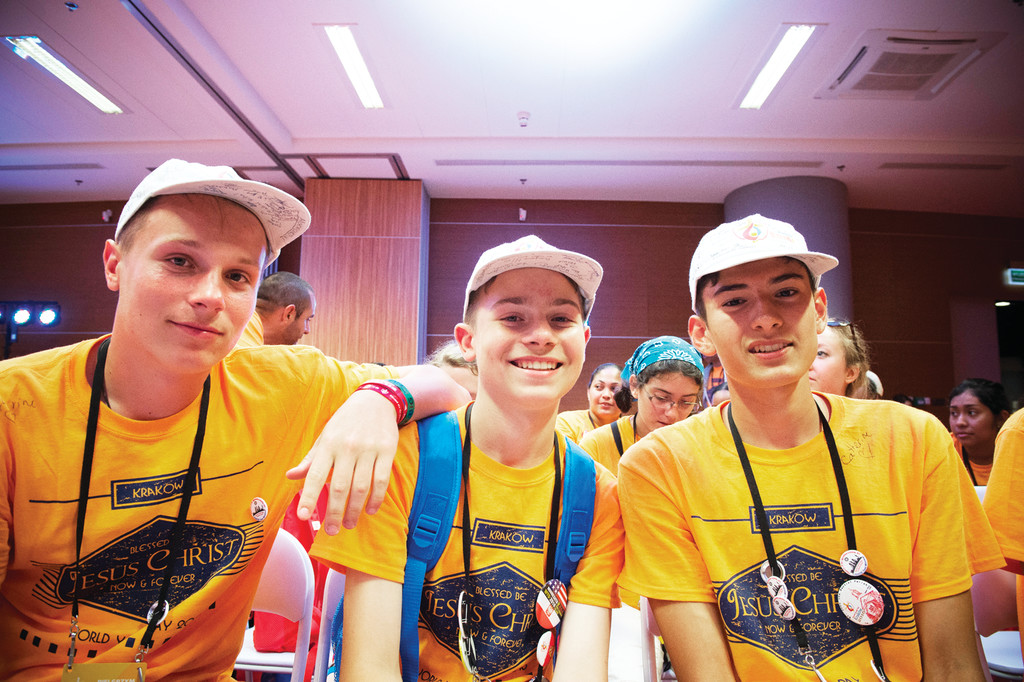 Wearing yellow T-shirts signifying that they are from the Archdiocese of New York, three boys sit in the Mercy Center in Krakow, which was sponsored by the Knights of Columbus during World Youth Day. The youths were there as part of the archdiocesan group that met with Cardinal Dolan July 28.