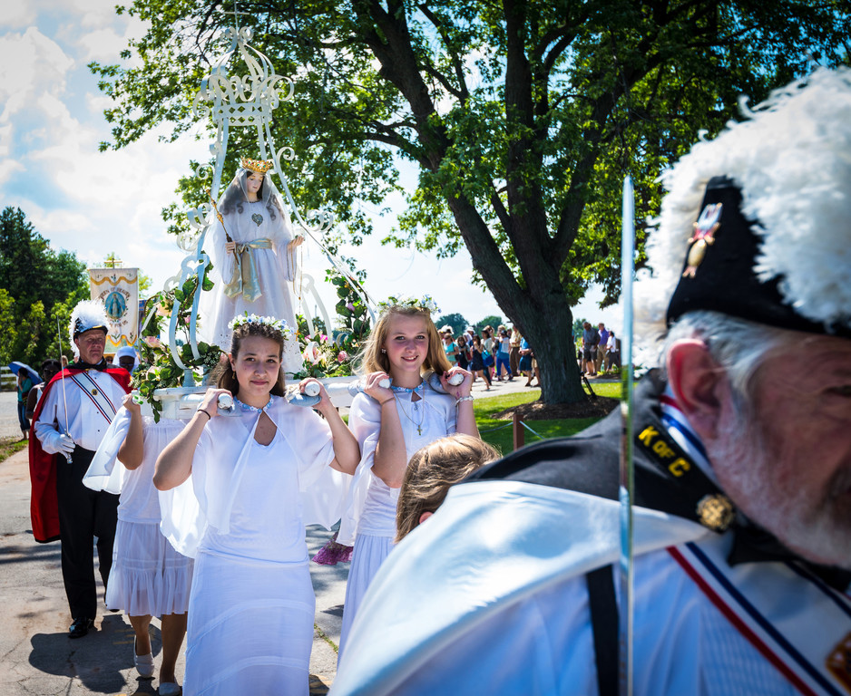 HONORING MARY—Morgan and Ashley Rabas help to carry a figure of the Blessed Mother following a well-attended outdoor Mass and Rosary procession at the Shrine of Our Lady of Good Help in Champion, Wis., on the feast of the Assumption, Aug. 15,  2015.