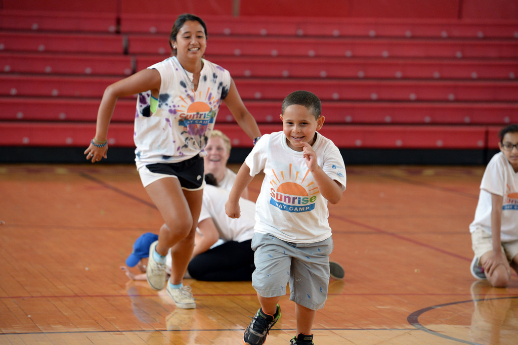 Summer fun is a sure thing at Sunrise Day Camp on Staten Island.  Ahmed Abdelsalam, a camper, runs ahead of Antoinette Chow, a camp counselor.