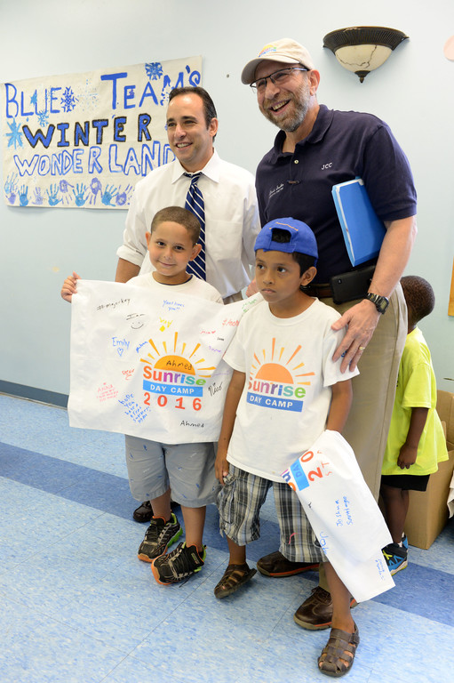 Ahmed Abdelsalam and Allejandro Regalado, a sibling of another camper, display their pillowcases alongside Vincent Ignizio, Catholic Charities of Staten Island CEO and David Sorkin, executive director of the Jewish Community Center of Staten Island.