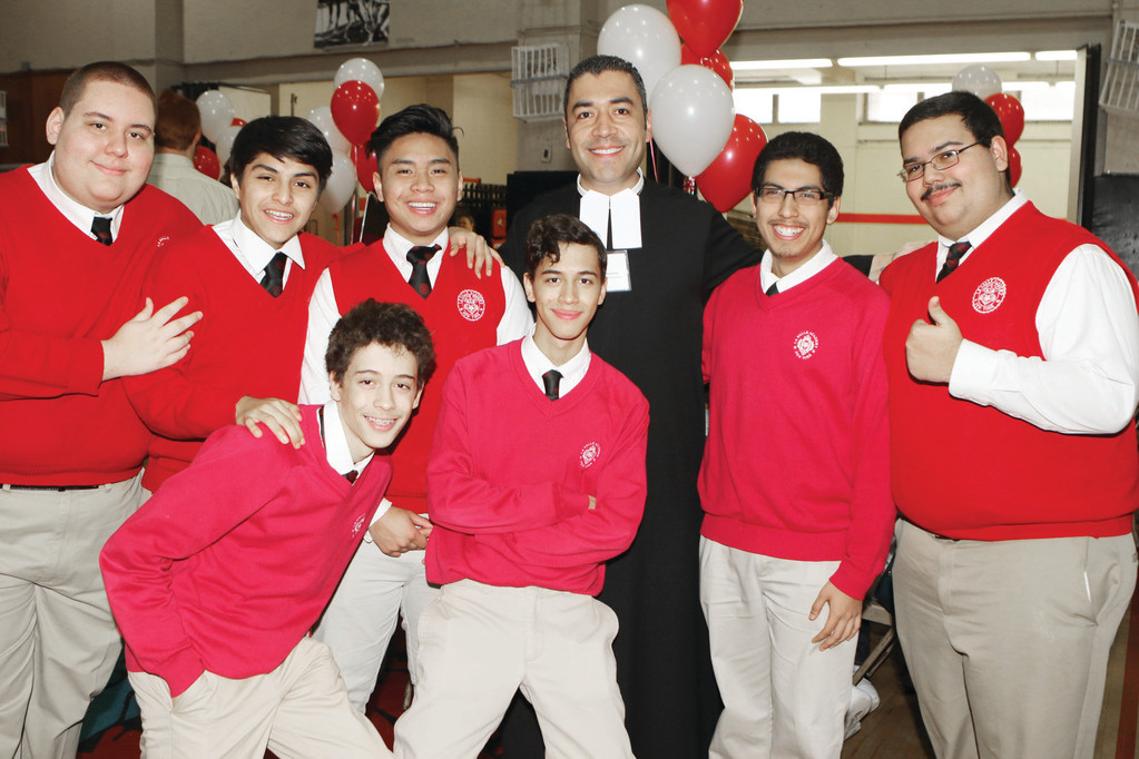 Top row from left, La Salle Academy seniors Matthew Perez, Derek Criollo, Jeremiah Katigbank, Christopher Cumbe and Jeremy Ferrer and, bottom row, twins Jancalo and Joshua Mediavilla, strike a joyful pose with Brother Anwar Martinez, F.S.C., a teacher at the boys' high school in Manhattan, where enrollment is on the rise.