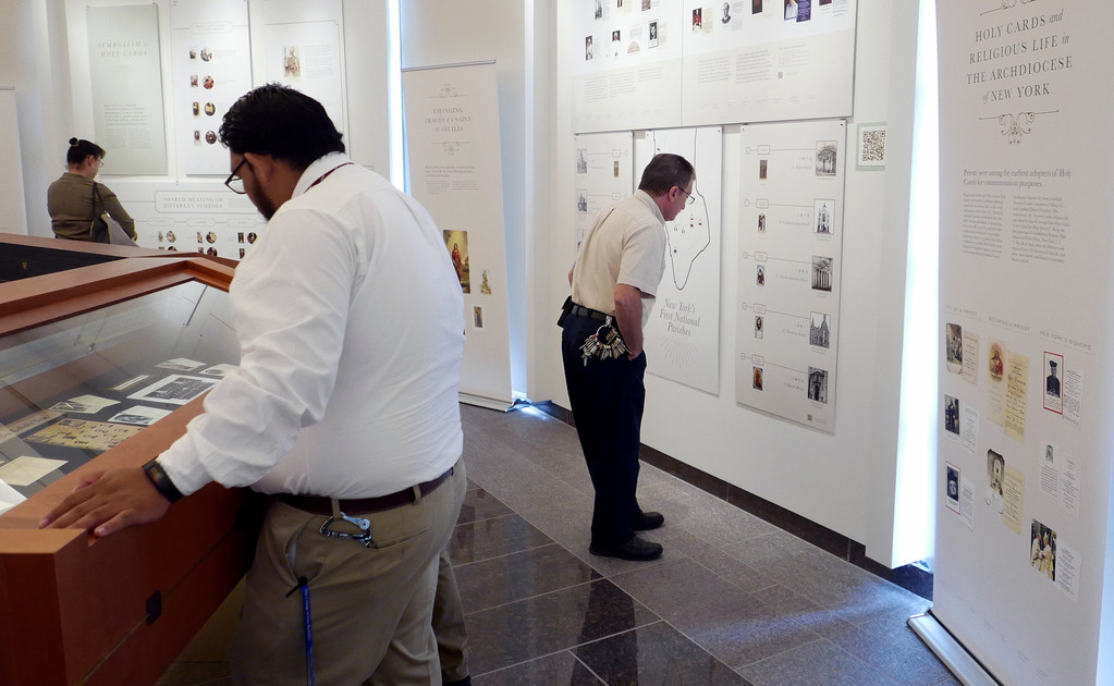 "LIVING HISTORY—visitors take a close look at the new exhibit, ""Images of Sanctity,"" mounted by the Archives of the Archdiocese of New York."