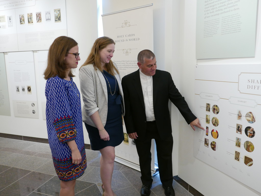 Many of the holy cards in the exhibit come from the personal collection of Father Eugene Carrella, pastor of St. Rita's parish, Staten Island, shown with Kate Feighery, center, archivist of the archdiocese, and Elizabeth Alleva, assistant archivist.