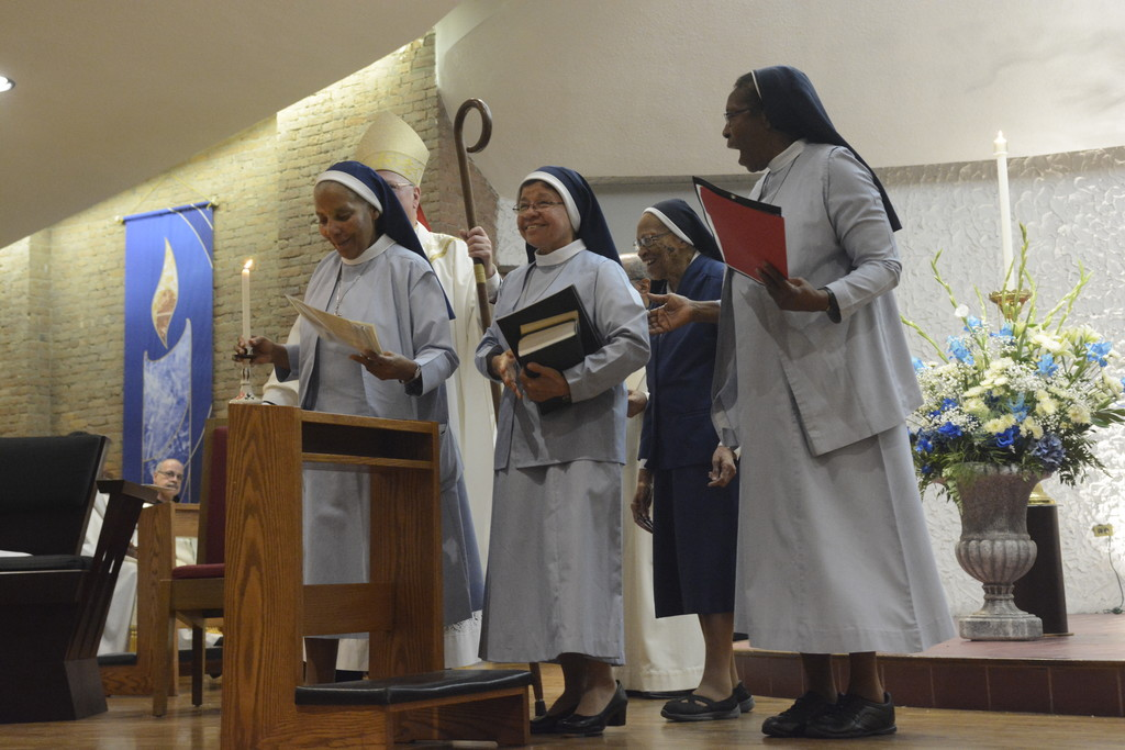 Sister Gertrude Lilly Ihenacho, F.H.M., congregation minister for the Franciscan Handmaids of the Most Pure Heart of Mary, far right, expresses joy for Sister Mary Ann Baichan, F.H.M., second from left, who professed first vows during a Mass celebrating the centennial of the order's founding. With them were, from left, Sister Charla Hill, F.H.M., at left, and Sister Loretta Theresa Richards, F.H.M., in background. Cardinal Dolan, partly obscured in photo, was the principal celebrant at the Oct. 8 Mass offered at St. Charles Borromeo Church in Harlem.