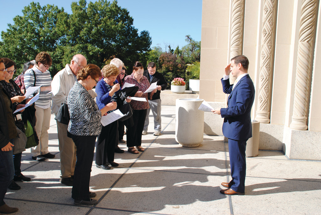 Daniel Frascella, director of adult faith formation for the archdiocese, leads pilgrims in prayer on the front steps of the basilica at the day's outset.