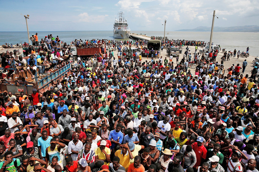 IN DESPERATE NEED—A large crowd in Jeremie, Haiti, wait for relief supplies to be unloaded from a Dutch navy ship on Oct. 16 following the heavy damage wrought by Hurricane Matthew.