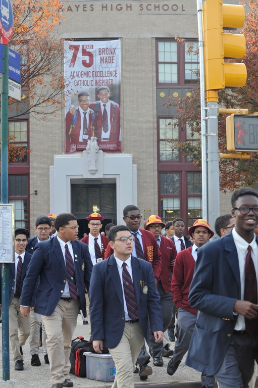 Cardinal Hayes High School in the Bronx is celebrating the 75th anniversary of its founding—a banner marking the occasion is seen above the entrance.