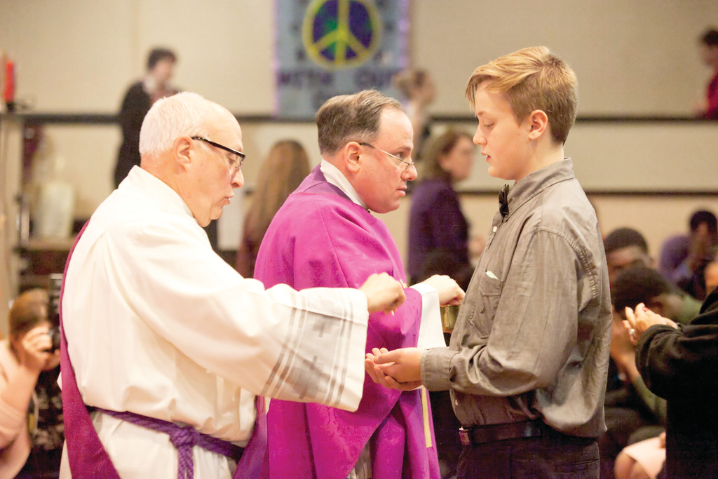 Teens receive Communion from Deacon Angelo Corsaro of Sacred Heart parish in Monroe and Father Martine.