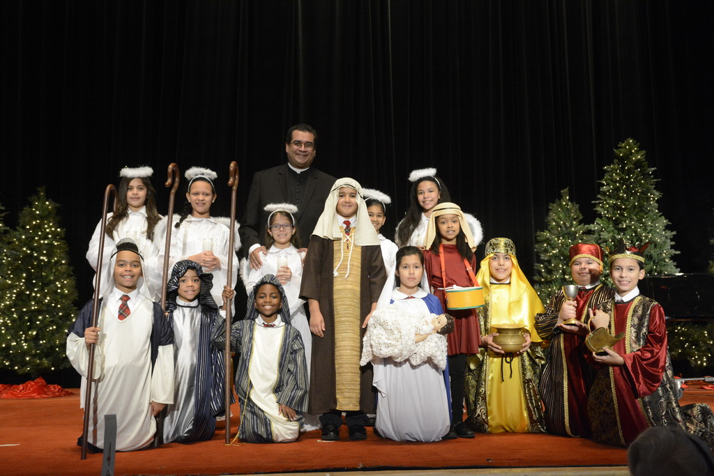 Father Eric Cruz, pastor of St. John Chrysostom parish in the Bronx, stands with students from St. John Chrysostom School following the 71st annual Cardinal's Christmas Luncheon at the Waldorf Astoria on Dec. 5.
