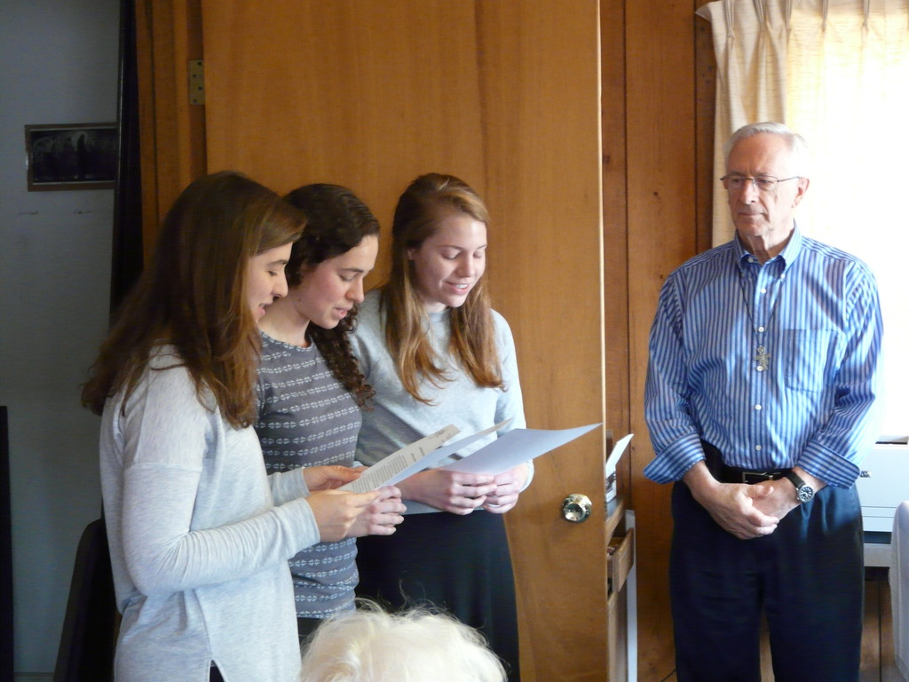 LAMP missionaries Samantha Chestney, Hailey Megge and Sarah Mutchler participate in a ceremony at Mass on Nov. 28 in which they each received a LAMP mission crucifix. At right is Tom Scheuring, co-director of LAMP Catholic Ministries.