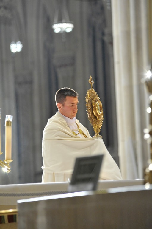 Deacon Michael Plona of the Diocese of Rockville Centre, who will be ordained in June, holds a golden monstrance containing the Blessed Sacrament during Adoration and Benediction before a Vigil Mass for the Feast of the Immaculate Conception at St. Patrick's Cathedral.