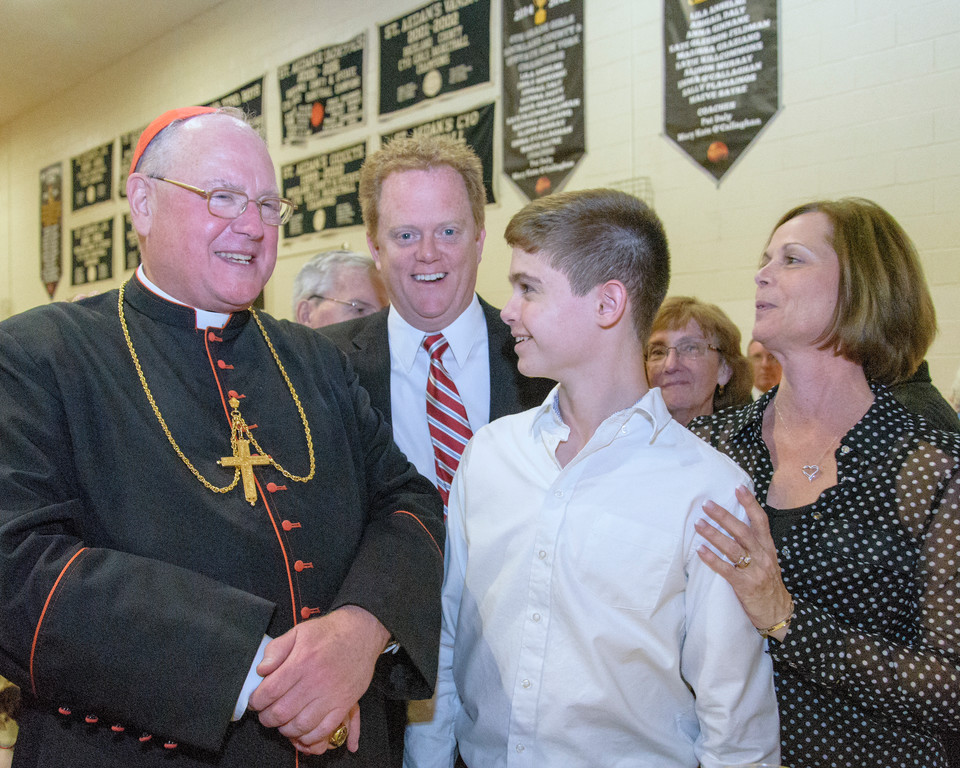 Cardinal Dolan greets Richard and Patricia Lenihan with their son Patrick, an altar server.