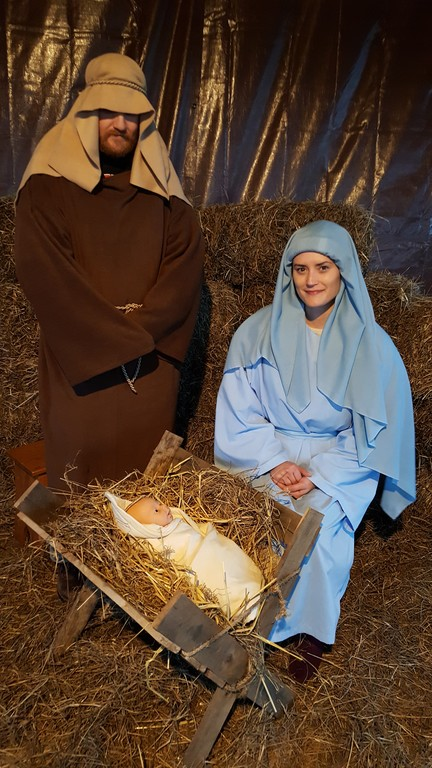 NATIVITY—Our Lady of the Assumption Church in Bloomingburg held its inaugural Presentation of the Live Nativity in the Father Jim Hess Pavilion on Dec. 3. Above, parishioners Rob Lawrence and Tanja Beemer portray St. Joseph and Mary overlooking the newborn Jesus. Other parishioners served as an angel, the Wise Men and two shepherds. A sheep and a lamb, belonging to local 4H members, also took part. The newly fashioned stable gave sufficient room for the parish choir to provide music during the first performance, and the Carmelite novices from Brandsma Priory in Middletown came to sing during the second performance. About 100 parishioners were in attendance. The church is a mission of Our Lady of Mount Carmel parish in Middletown.