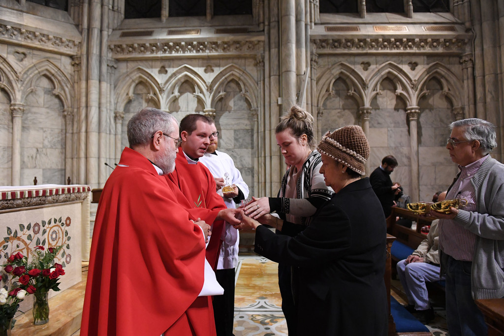GIFTS—Father Jamie Dennis, who is blind, accepts the offertory gifts at the Mass he celebrated for the Feast of St. Lucy in the Lady Chapel of St. Patrick's Cathedral. Presenting the gifts were Carmen Gomez and Richard Baldelli, who were assisted by Aisling Redican. At left is Father John Sheehan, S.J.