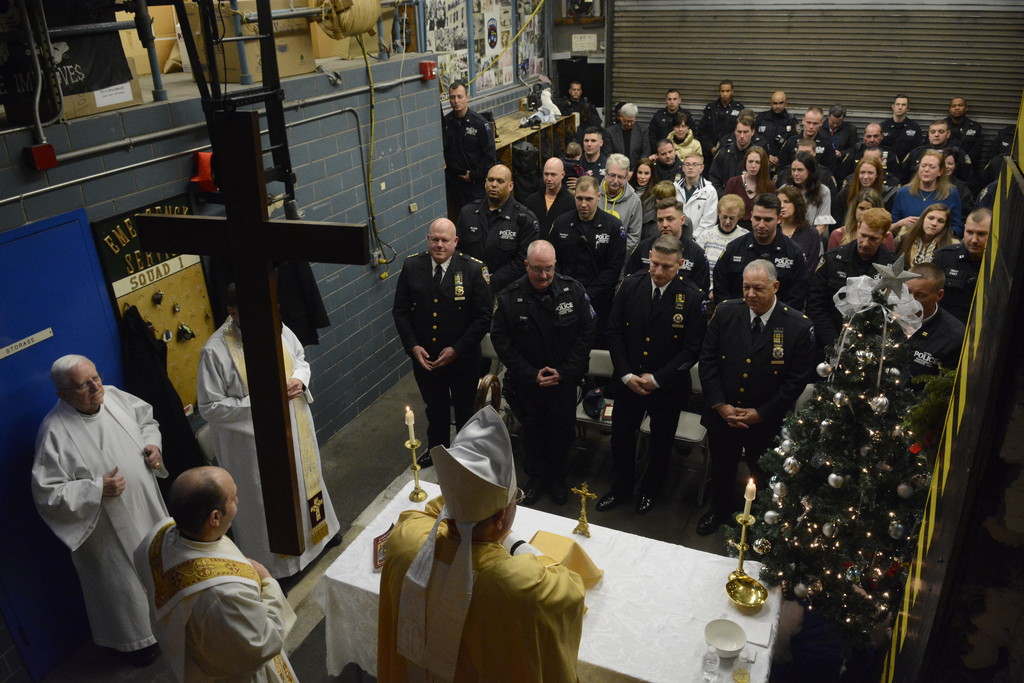 Cardinal Dolan celebrated a special Christmas Eve Mass in the garage bay of Emergency Service Truck 1 in Manhattan for officers from Emergency Service Unit (ESU) Squad 1, officers of other ESU squads and New York Police Department officers from the neighboring 13th Precinct. In the first row are Thomas Purtell, NYPD Chief Citywide Operations; Sgt. Mike Kenny, NYPD ESU; Lt. Michael McGuinness, ESU Truck 1 supervisor; Deputy Chief Vincent Giordano, Commanding Officer of ESU; and Capt. Ronald Zedalis, ESU Duty Captain, partially hidden.