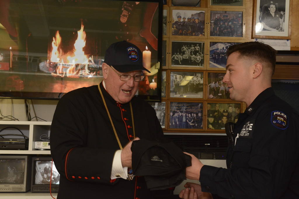 New York Police Department Emergency Service Truck 1 Detective Brian Glacken gives Cardinal Dolan an NYPD shirt, and a hat, which the cardinal immediately placed on his head. The cardinal visited the Emergency Service garage in Manhattan to celebrate Mass for officers working on Christmas Eve, Dec. 24.