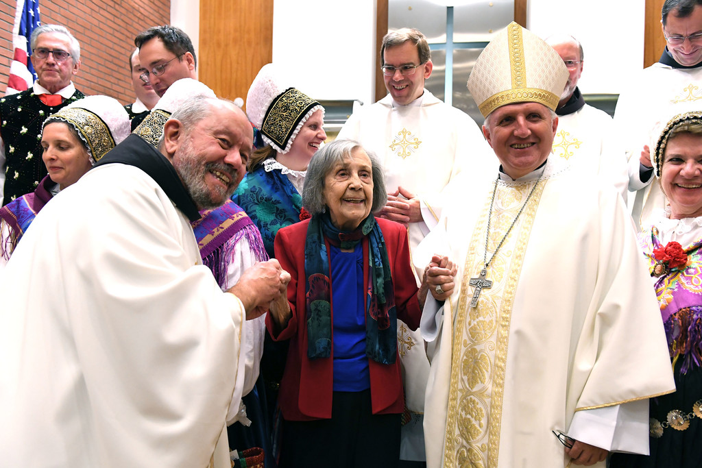 Father Krizolog Cimerman, O.F.M., pastor of St. Cyril's, left, and Archbishop Stanislav Zore of Ljubljana, right, assist 99-year-old parishioner Myra Hesch. In the background is Father Marjan Cuden, O.F.M., provincial of the Slovenian Province of the Holy Cross.