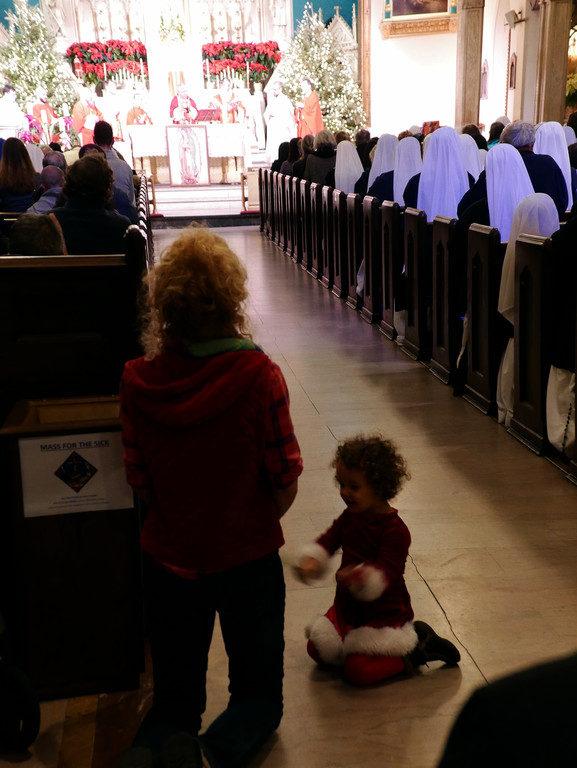 A young child kneels near her mother in a crowded Holy Innocents Church as Auxiliary Bishop John O'Hara celebrates Mass for the Feast of the Holy Innocents on Dec. 28.