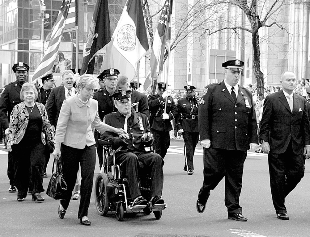 IN UNIFORM—NYPD Detective Steven McDonald is joined by his wife Patti Ann, along Manhattan's Fifth Avenue, after an April 2007 Mass at St. Patrick's Cathedral. McDonald was honored as the NYPD Holy Name Society Man of the Year. Walking with them were then-Police Commissioner Raymond Kelly, right, and, in uniform, Sgt. Brian P. Reilly, president of the Holy Name Society of Manhattan, the Bronx and Staten Island.