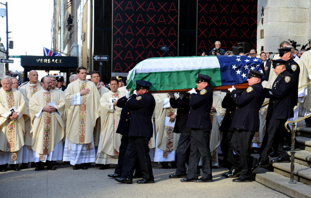 Members of the New York Police Department honor guard carry the casket of Detective Steven McDonald from St. Patrick's Cathedral after his Jan. 13 Funeral Mass as priests and thousands of his fellow police officers stood respectfully in front of the cathedral and along Fifth Avenue. Detective McDonald, who was shot and paralyzed on duty 30 years ago, died Jan. 10.