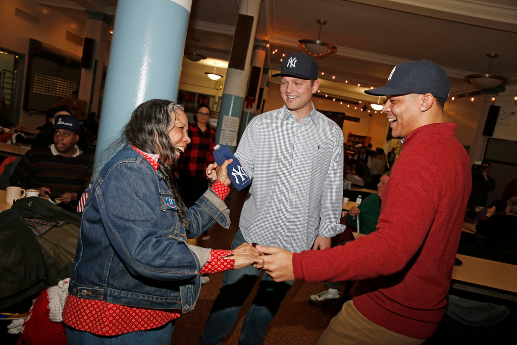 Chance Adams and Justus Sheffield, two top Yankees prospects, greet a senior at Encore Senior Center at St. Malachy's Church in Manhattan Jan. 18. The Yankees served lunch and later danced with the seniors at Encore's monthly birthday party as part of the organization's first Winter Warm Up.