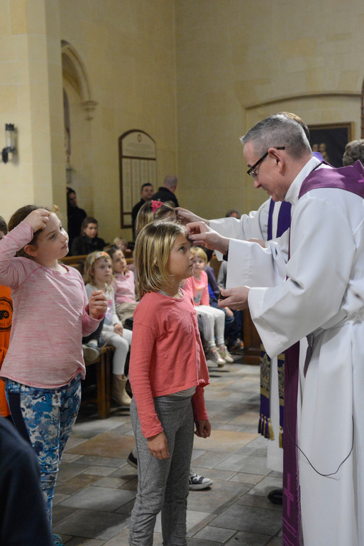 Charlotte Phillips, a third-grade religious education student at St. Joseph's, receives ashes from Father Peter McGeory, pastor, during the first of three prayer services for students and parishioners at the Bronxville church on Ash Wednesday.