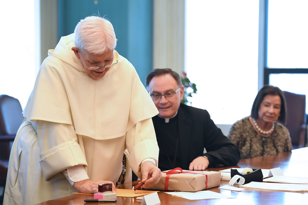 Father Gabriel O'Donnell, O.P., drops sealing wax onto an envelope with Msgr. Robert Hospodar and Valerie Mastronardi watching as the archdiocese closed its cause and mailed documents for officials in Rome to consider in the canonization cause of Father Paul Wattson, S.A.