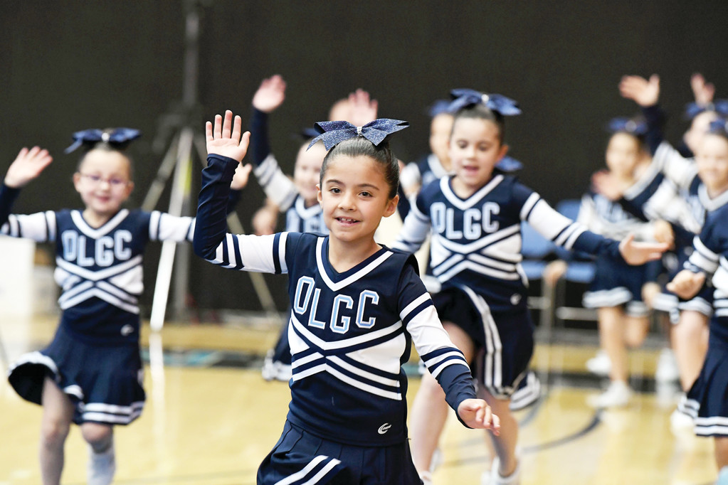 Second-grader Francesca DelBaso leads Our Lady of Good Counsel during the introduction for their routine.