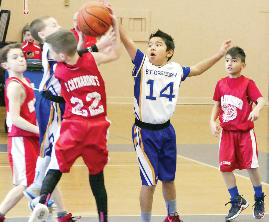 Matthew McCoy and Evan Schwartz, right, of St. Gregory Barbarigo, Garnerville, battle Grady Lennon of St. Catharine, Blauvelt, for the basketball in the third-grade boys' championship game at Mount St. Michael Academy in the Bronx.