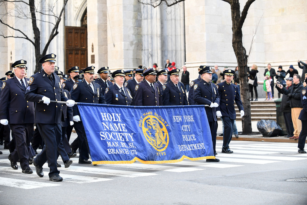 Members of the New York Police Department's Holy Name Society for Manhattan, Bronx and Staten Island walk behind their banner after attending the 8 a.m. Mass at St. Patrick's Cathedral March 19.