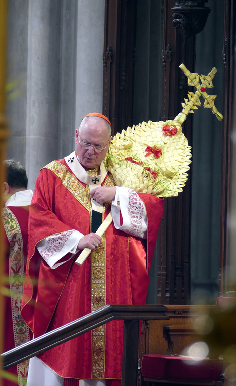 PALM SUNDAY—Cardinal Dolan carries palm fronds ornately fashioned in the form of a cross during Palm Sunday Mass he offered April 9 at St. Patrick's Cathedral.