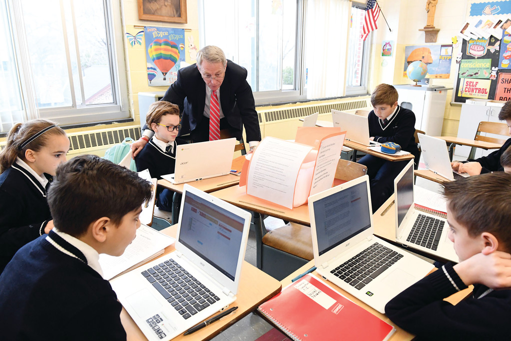 Dr. Timothy J. McNiff, superintendent of schools in the archdiocese, looks at the laptop of student Jake Giordano in a fifth-grade social studies class. The April 7 open house at St. Charles School on Staten Island enabled education leaders and representatives from the Richmond County Savings Foundation to see firsthand how blended learning is working there.