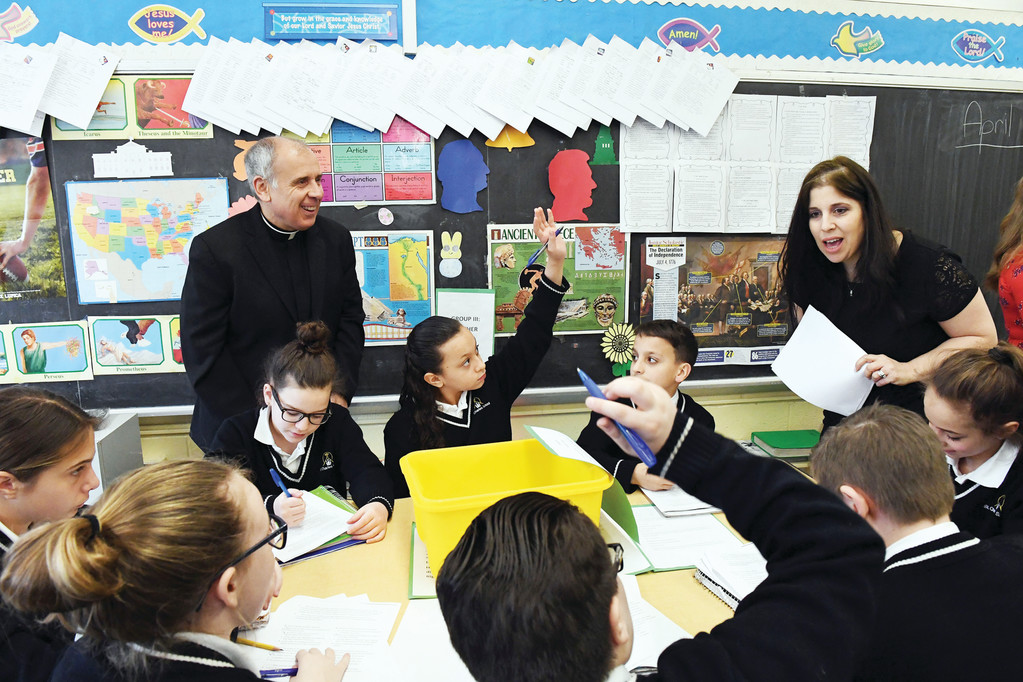 Father Louis Jerome, pastor of St. Charles parish, watches Nicole Colacci work with students in her fifth-grade social studies class at St. Charles School during an open house for education leaders and representatives from the Richmond County Savings Foundation to see blended learning in action April 7.