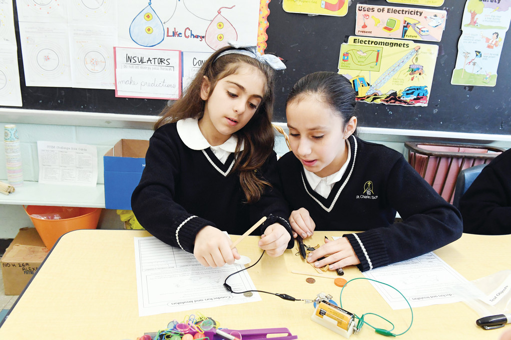 Students Julie Tagliani and Nicole Medina work with electrical testers in their fourth-grade science class to find out whether they are insulators or conductors.