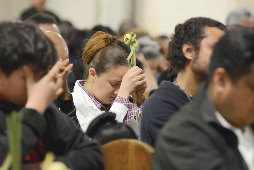 A parishioner holds up palms while praying during Palm Sunday Mass at St. Peter's Church in Yonkers April 9.