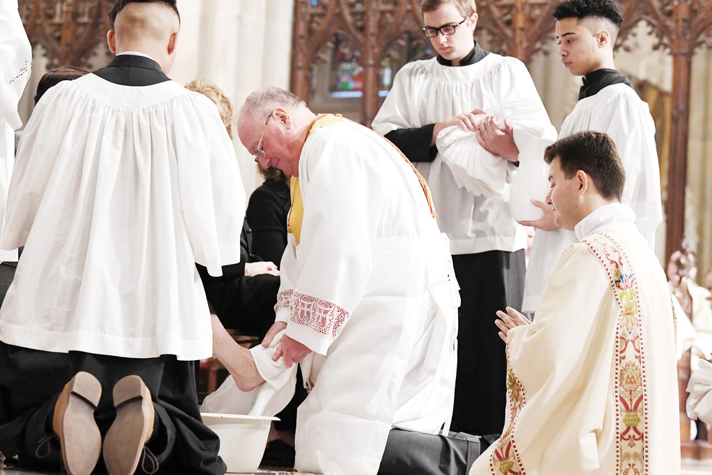 Cardinal Dolan performs ritual foot-washing in imitation of Jesus on Holy Thursday.