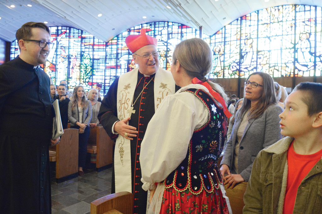 Cardinal Dolan and Father Szymon Kurpios greet a young woman in native Polish dress at St. James the Apostle.