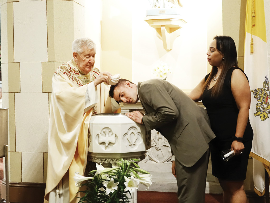 Msgr. J. Christopher Maloney, pastor of St. John the Baptist and Most Holy Trinity parish, baptizes Seth Marchewka, with his godmother Wendy Rodriquez, during the Easter Vigil Mass.