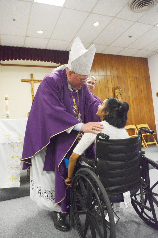 BLESSING—Cardinal Dolan blesses resident Bridgette Nathan, who is preparing to travel to Rome, during a Mass at Ferncliff Nursing Home in Rhinebeck April 12. Ms. Nathan and other individuals battling Huntington's disease will join Pope Francis at a papal audience at the Vatican May 18.