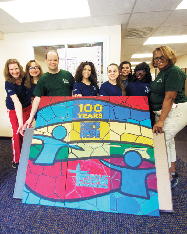 Volunteers display a mural they put together from their individually painted pieces at the Catholic Charities Community Services Putnam County office in Brewster. Holding the mural are, from left, case manager Marianna Duenas, Angelique Kortright, Leslie Askew, Nyla Elington, Lucianna Gallagher, Michelle Kelly, Kayla McGrath and Tamara Kirkman.